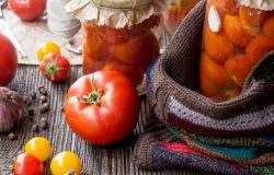 Fresh Tomatoes Beside Jars of Canned Tomatoes